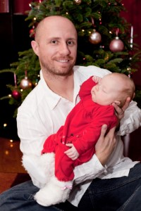 Dad holding sleeping baby in front of Christmas Tree