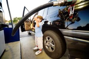 boy outside car at petrol station