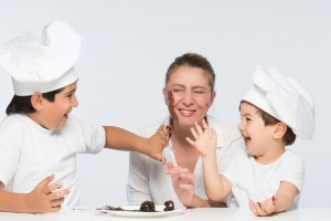 Family with mother and sons having joyful moments in kitchen wit